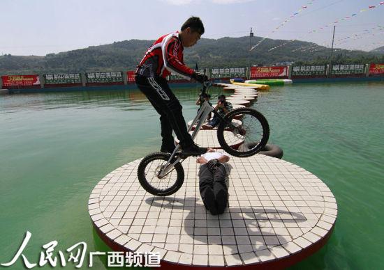 一名青年在进行水上车技表演。