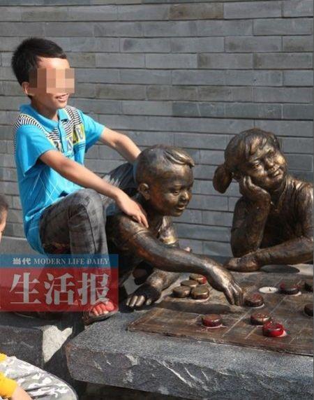 这位小朋友骑在景观雕塑上拍照留影。图片来源:当代生活报