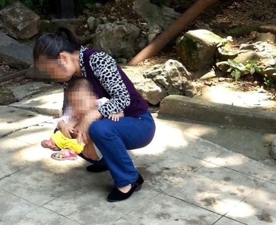 一位母亲在路边给孩子把尿。图片来源:当代生活报