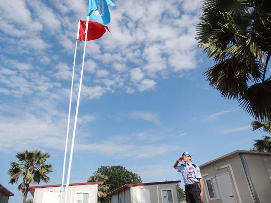 营区中央,旗杆肃立,直耸蓝天,五星红旗和联合国会旗迎风飘扬。