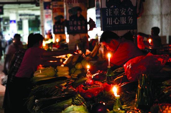 10月10日晚7时许,顾客和商户借着微弱的烛光的节能灯交易。南国早报记者邹财麟 摄