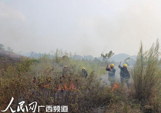 消防官兵在山脚扑灭余火。图片来源:人民网