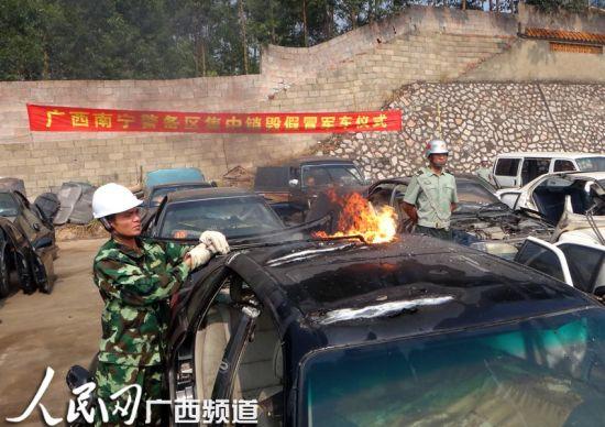 工作人员手持焊枪销毁假军车。图片来源:人民网