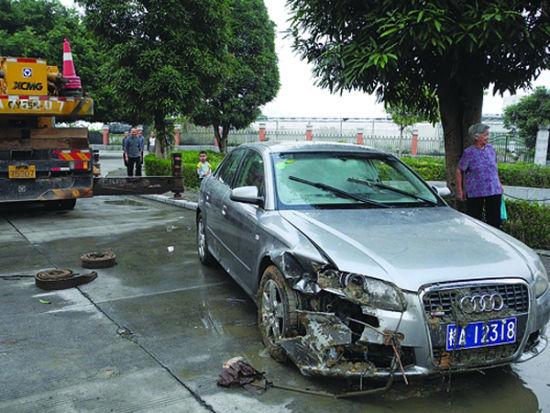 被吊上来的奥迪车停在路边。
