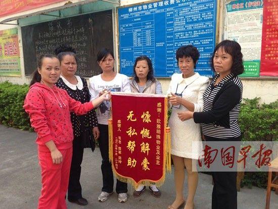 田明生家人(左二至左四)给小区业主代表和物管工作人员送来锦旗和感谢信。记者 陈枫 摄