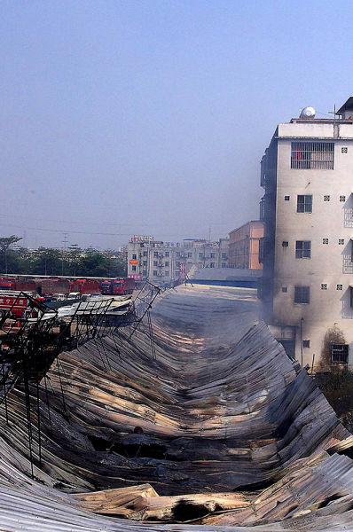 被烧穿的连排汽修店屋顶。有目击者称,火炬是从穿孔处冒出来的。南国早报记者 李俭芹 摄