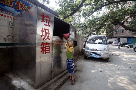 在西乡塘区位子渌社区,一位小朋友将垃圾袋装后投入封闭式垃圾箱。南国早报记者 苏华 摄
