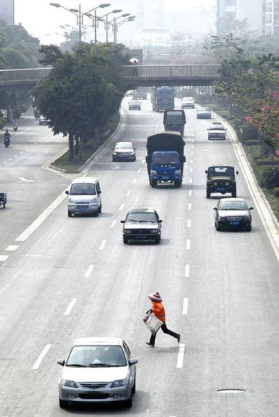 在秀厢大道,一名环卫工人在清理隔离带的垃圾后一路小跑返回安全地。