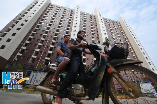 居住在公共租赁住房小区内的两名外来务工青年骑车外出。新华社记者 黄孝邦 摄