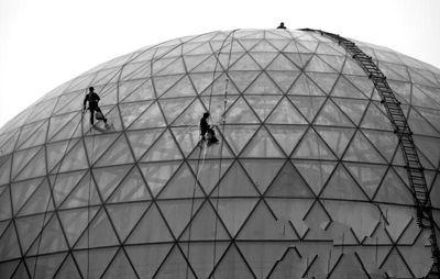 昨日下午3时,西安市长安南路,陕西自然博物馆球形玻璃外立面上,工人正在雾霾中施工。污染天气下,户外工作时,要做好防护措施。记者 黄利健 摄