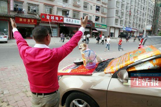 王江用身体语言来吸引市民注意。当代生活报记者 何学俏 摄