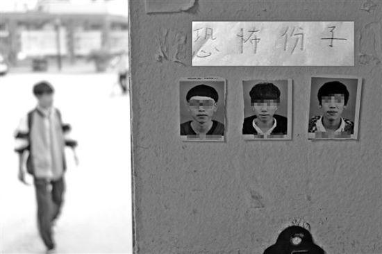 """单寸照片的上方原先贴有"""" 恐怖份子""""字样纸条,后有人将纸条撕走。温州都市报记者 王诚 摄"""