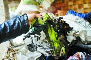 丁先生指示家中被烧毁的衣物。兰州晨报记者 陈若梦 摄