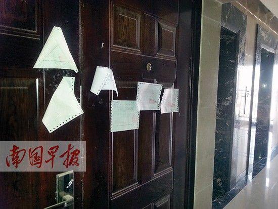 在财富国际广场小区,一业主家的门上贴了很多催费通知。