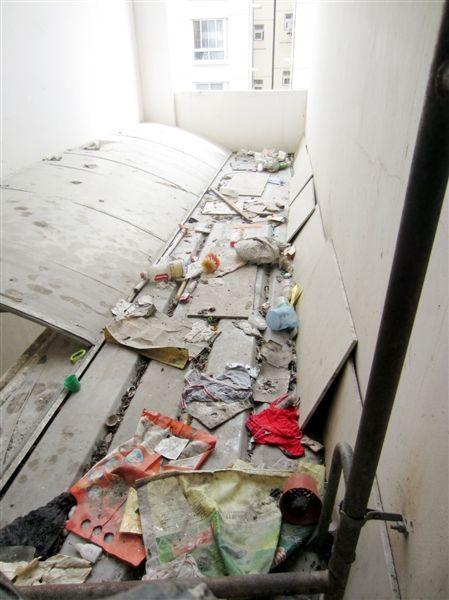 胡女士家窗下的挡棚上满是垃圾。 何声春 摄
