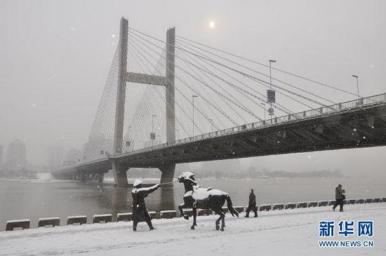 11月17日,行人冒雪行进在吉林省吉林市头道码头的街道上。新华社 王明铭 摄