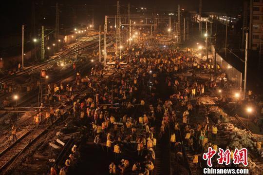 11月18日凌晨2时开始,3000多名工人在广西柳州高铁火车站,进行驳接轨道、填补道砟、调试信号等工作。 谢裕增 摄