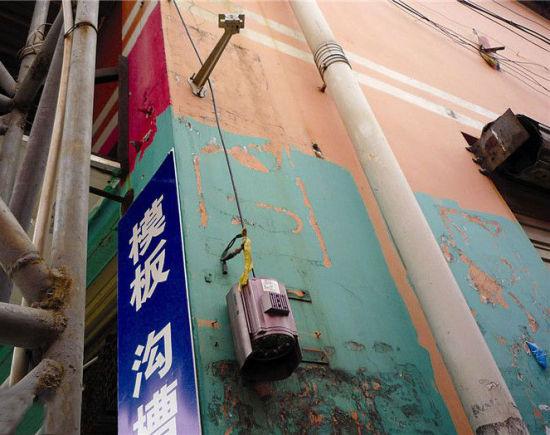 市场一个出入口处的电子眼遭到破坏,从铁架上脱落下来被电线吊着。南国早报记者 王艳群 摄
