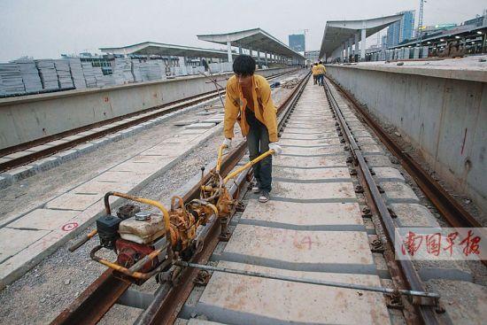 工人用机器将铁轨上的螺母固定起来。南国早报记者 邹财麟 摄