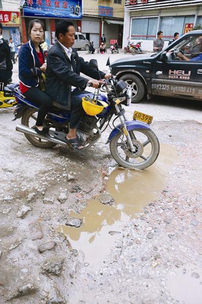 老五一西路约有1公里坑坑洼洼的路面,行人、车辆通行不便。南国早报记者 唐辉吉 摄