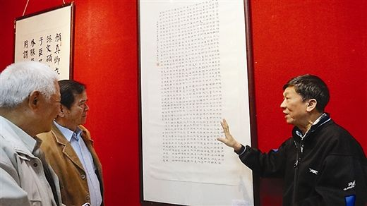 图为杨钦武(右)向观众介绍自己的临帖书法作品。南国早报记者 刘山 摄