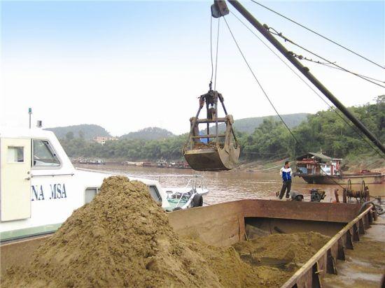 图为一艘超载采砂船被强制卸载。黄文彩 摄