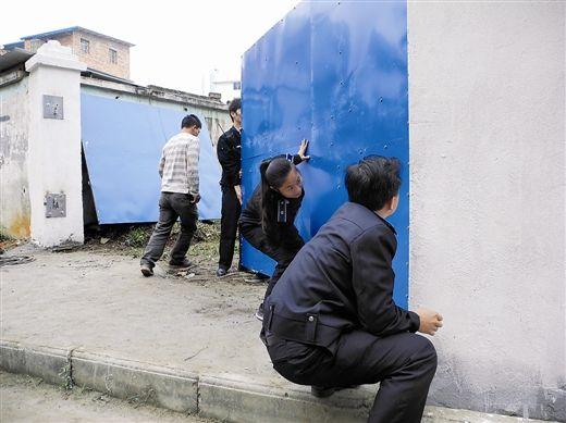 图为西乡塘区城管执法人员在工地帮助施工方安装铁门。 南国早报记者 程浩楠 摄