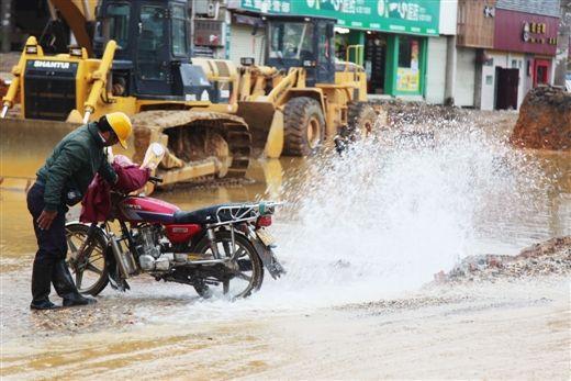 图为市民在漏水处洗车。当代生活报 记者 何学俏 摄