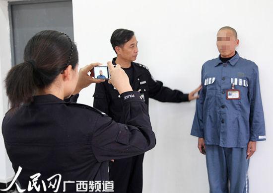 图为民警在钦州监狱帮服刑人员林某照相办证。