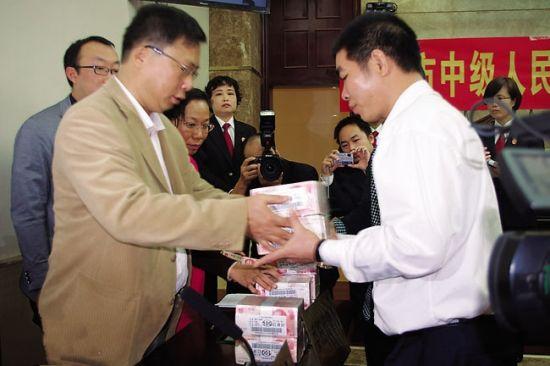开发商(左)当庭赔偿业主代表违约金。南国早报记者 李俭芹 摄