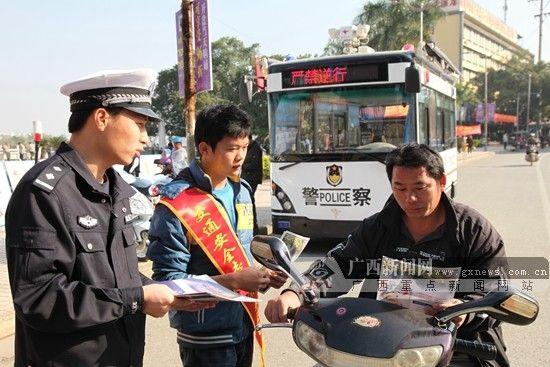 交警向电动车主宣传交通安全知识。崇左交警供图