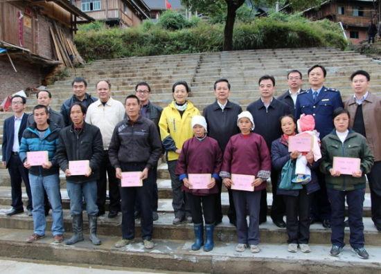 自治区人大副主任覃瑞祥、自治区工商局张虹局长向林略村学生家长代表发放红盾奖学金。
