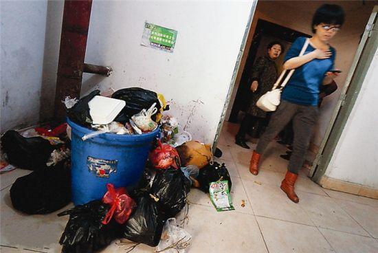 电梯难等,一些业主爬楼回家,楼道里堆满垃圾。图片来源:南国早报