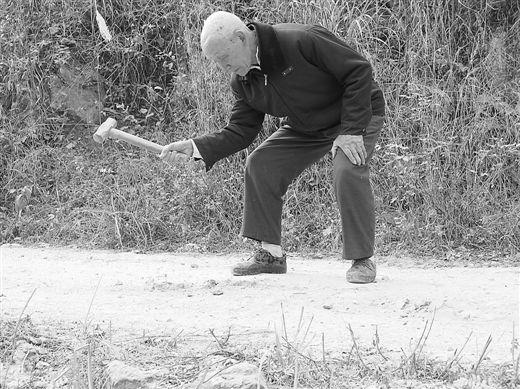 图为谢用民用锤子修平路面上突出的石头。