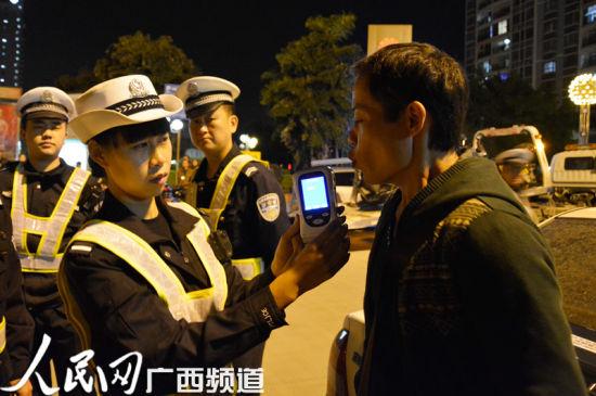 民警对驾驶员进行酒精测试。图片来源:人民网