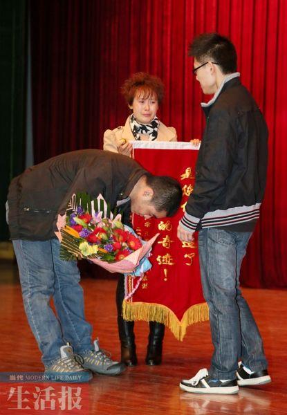 来自四川的王鹏程夫妇向北海捐助者唐运广鞠躬致谢。当代生活报记者 周军 摄