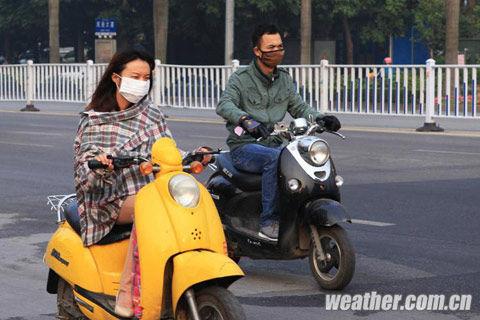 南宁市雾霾中出行的骑车族用口罩防护。(摄影:马继华)