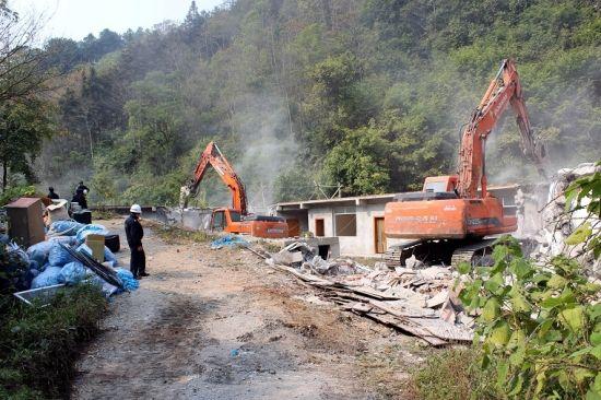 图为工作人员正在拆建在深山中的违建房屋。 邓湖广 摄