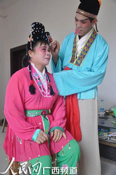 彩调队队长李树光在为妻子化妆