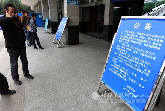 10日下午,桂林火车站售票大厅前,一些旅客正在关注部分路线暂时停运的信息。桂林晚报记者 李凯 摄