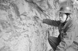 图为宁明县文物管理所所长朱秋平在勘察一处被石灰石沉积覆盖的岩画。新华社记者 张爱林 摄