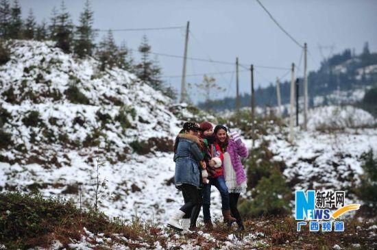 12月16日,在广西隆林各族自治县德峨镇,游人雪地里拍照留念。新华社记者 黄孝邦 摄