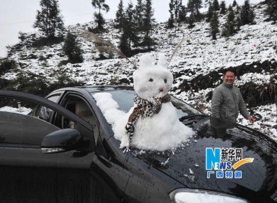 在广西隆林各族自治县德峨镇,一位车主在车头上堆起一个雪人。新华社记者 黄孝邦 摄