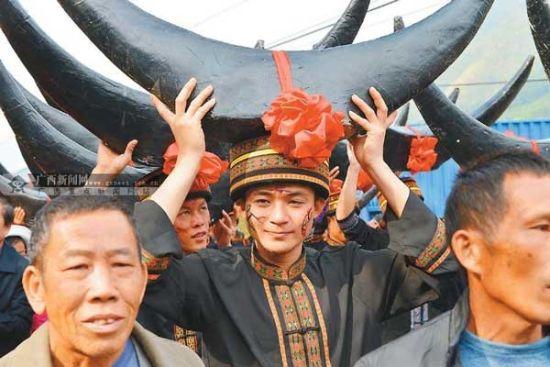 """瑶民顶着巨大的""""牛角""""前来参加活动,他们视牛为农家之宝"""