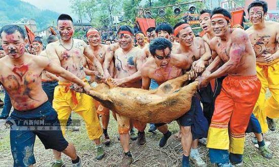 """充满原生态的""""傩面抢金猪""""活动再现了古瑶民的原始狩猎生活"""
