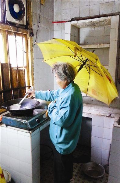 老人每天都得这样撑着伞做饭。