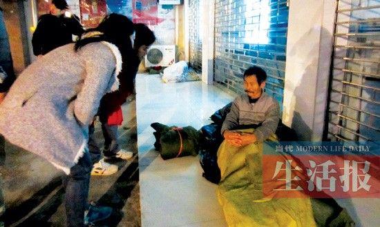 义工们在民乐新民路口与一位流浪汉交流,表示可以向其提供援助。见习记者 叶丽萍 摄