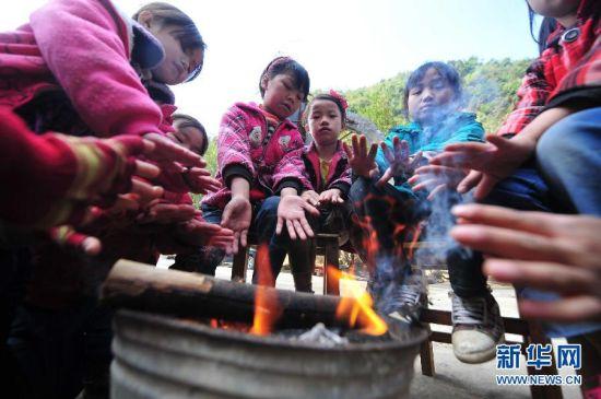 学生们课间在教室外烤火取暖,抵御寒冷。新华社记者 黄孝邦 摄