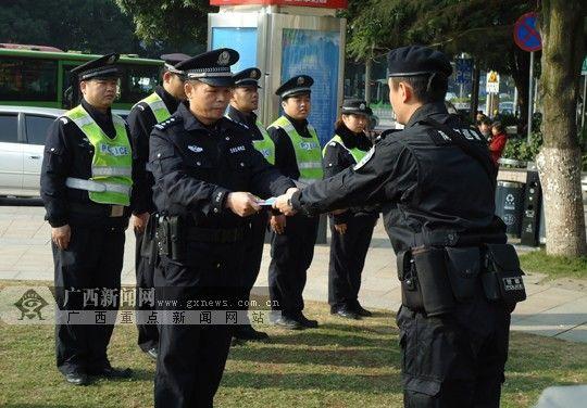 青秀公安分局民警(左)向巡警支队民警交接警务站工作。广西新闻网实习生 曾鑫滔 摄