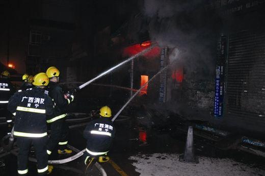 消防员出水扑灭五金店的火势。 黄善钊 摄